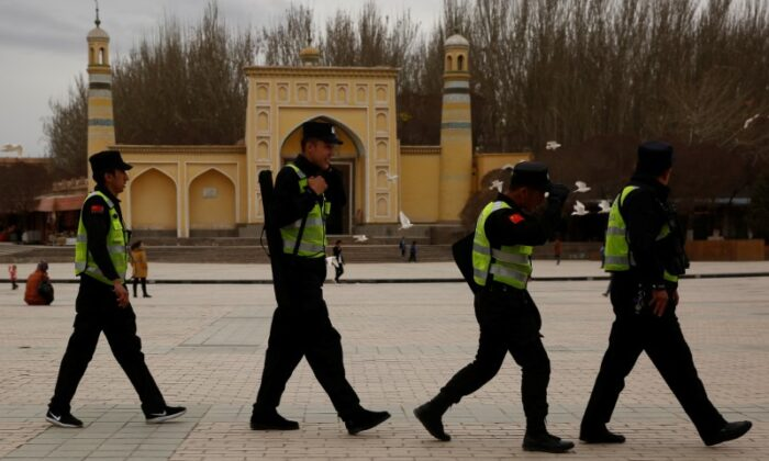 Police patrol walk in front of the Id Kah Mosque in the old city of Kashgar, in Xinjiang, China on March 22, 2017. (Reuters/Thomas Peter)