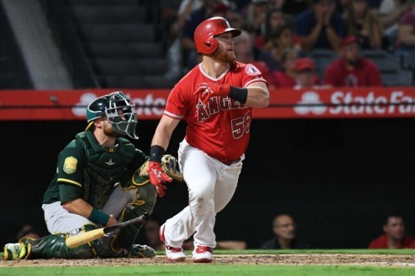 Los Angeles Angels right fielder Kole Calhoun hits a two-run home run in the third inning against the Oakland Athletics.