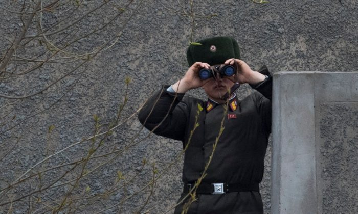 A North Korean soldier uses his binoculars to look across the Yalu river near Sinuiju, on April 14, 2017. (Johannes Eisele/AFP/Getty Images)