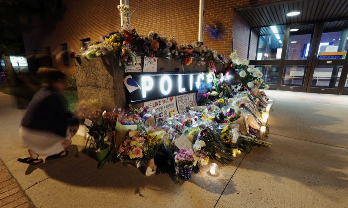 Fredericton residents pay their respects at a makeshift shrine created in front of police headquarters after four people, including two police officers, were killed in a shooting in Fredericton, the capital of the province of New Brunswick, Canada, August 10, 2018. (Reuters/Dan Culberson)