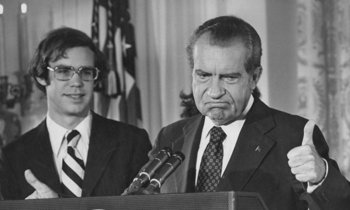 Former President Richard Nixon (1913 - 1994) gives the thumbs up as he addresses the White House staff upon his resignation as 37th President of the United States, Washington, Aug. 9, 1974. His son-in-law David Eisenhower is with him on the left. The Washington Post demonstrated the power of the media by doing reporting that helped force Nixon's resignation. (Keystone/Hulton Archive/Getty Images)