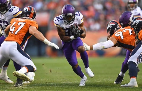 Minnesota Vikings running back Roc Thomas carries the ball between the tackles of Denver Broncos linebacker Josey Jewell and defensive end Adam Gotsis in the first quarter.