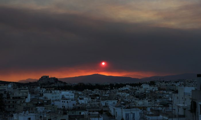 The sun sets over Athens and its ancient Acropolis (L) as a thick cloud of smoke levitates over the Greek capital, caused by a forest fire, fanned by strong winds on the island of Evia, in Athens, Greece, Aug. 12, 2018. (Reuters/Yannis Behrakis)