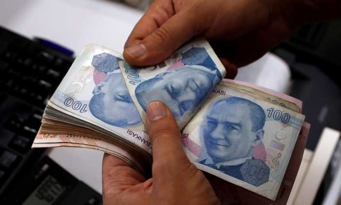 A money changer counts Turkish lira banknotes at a currency exchange office in Istanbul, Turkey on Aug. 2, 2018. (Reuters/Murad Sezer/File Photo)