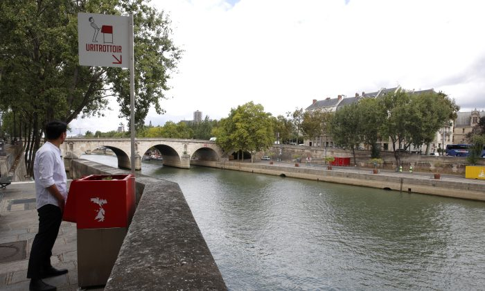 A man stands in front of a bright red eco-friendly urinal on the Ile Saint-Louis along the River Seine in Paris on Aug. 13, 2018. (Reuters/Philippe Wojazer)