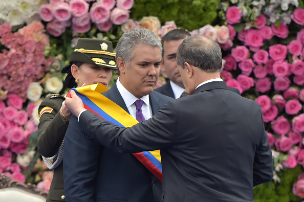 Colombia's new President Ivan Duque (L) receives the presidential sash from Senate President Ernesto Macias during his inauguration ceremony at Bolivar Square in Bogota, on Aug. 7, 2018. (RAUL ARBOLEDA/AFP/Getty Images)