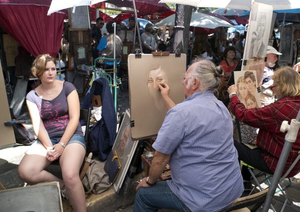 A painter draws the portrait of a tourist on July 13, 2013 at the Place du Tertre square near the Sacre-Coeur basilica in the Montmartre neighborhood of Paris. (PATRICK KOVARIK/AFP/Getty Images)