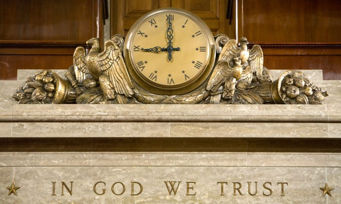 """A clock and the motto """"In God We Trust"""" over the Speaker's rostrum in the U.S. House of Representatives chamber in Washington on Dec. 8, 2008. (Brendan Hoffman/Getty Images)"""