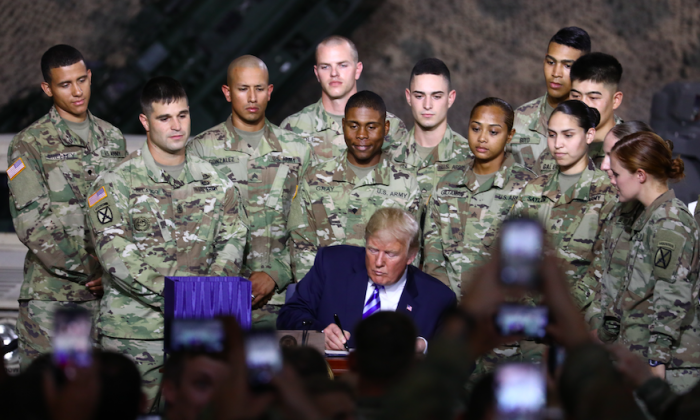 President Donald Trump signs the 2019 National Defense Authorization Act at the Wheeler-Sack Army Airfield in Fort Drum, N.Y., on Aug. 13, 2018. (Charlotte Cuthbertson/The Epoch Times)