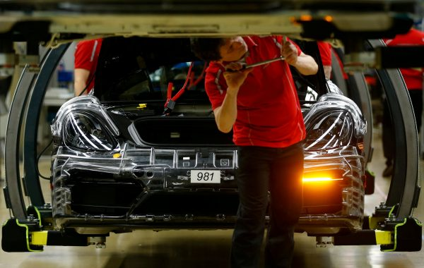 A worker at a Porsche assembly plant tightens a bolt on a vehicle