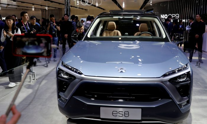 Visitors check NIO ES8 displayed during a media preview of the Auto China 2018 motor show in Beijing, China April 25, 2018. REUTERS/Damir Sagolj