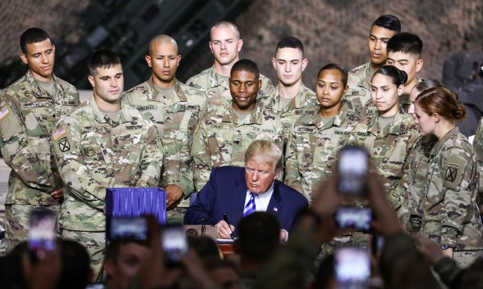 President Donald Trump signs the 2019 National Defense Authorization Act at Wheeler-Sack Army Airfield at Fort Drum, N.Y., on Aug. 13, 2018. (Charlotte Cuthbertson/The Epoch Times)