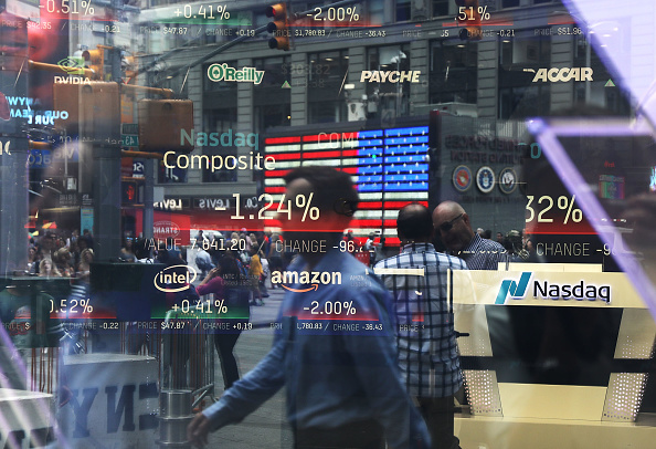 People are reflected in the window of the Nasdaq MarketSite in Times Square, New York on July 30, 2018. (Spencer Platt/Getty Images)