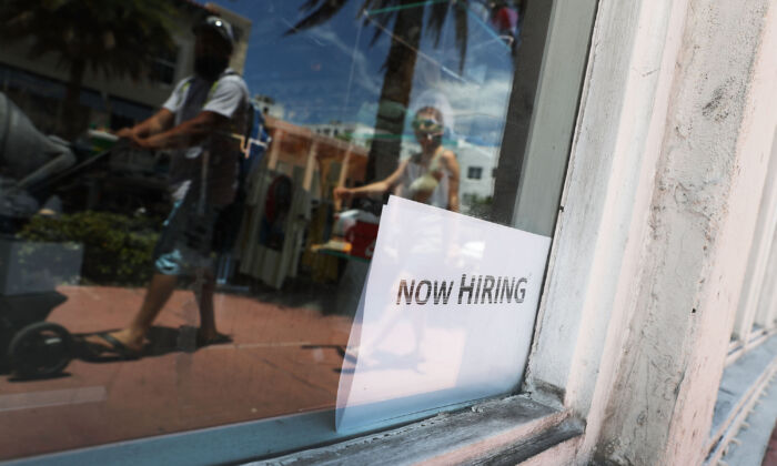 A now hiring sign is seen in a window of a business in Miami on July 7, 2017. (Joe Raedle/Getty Images)