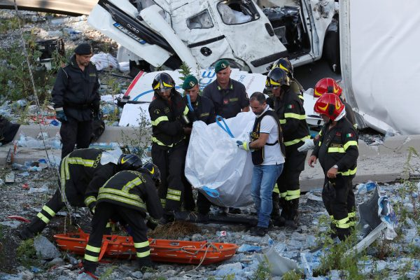 Firefighters carry a body from the rubble of the collapsed bridge
