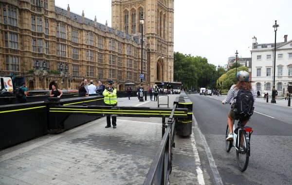 A cyclist passes a police officer standing at the vehicle barrier to the Houses of Parliament