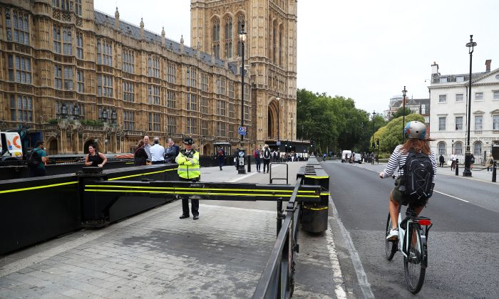 A cyclist passes a police officer standing at the vehicle barrier to the Houses of Parliament where a car crashed after knocking down cyclists and pedestrians in Westminster, London on Aug. 15, 2018. (Reuters/Hannah McKay)