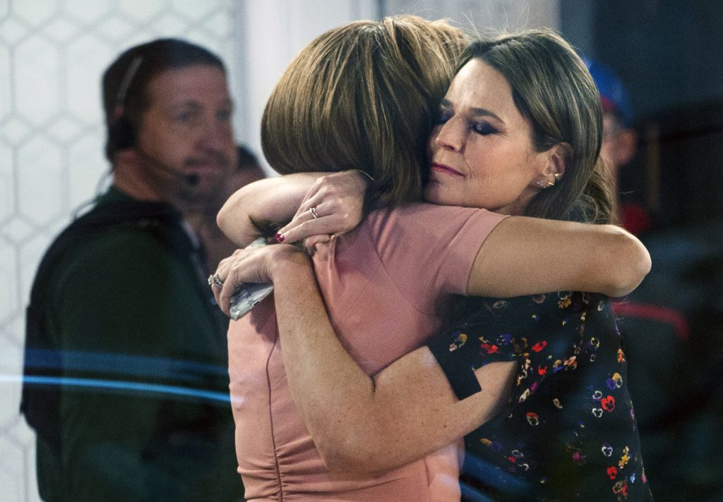 """Co-anchors Hoda Kotb, left, and Savannah Guthrie embrace on the set of the """"Today"""" show in New York, after NBC News fired host Matt Lauer, on Nov. 29, 2017. (AP Photo/Craig Ruttle)"""