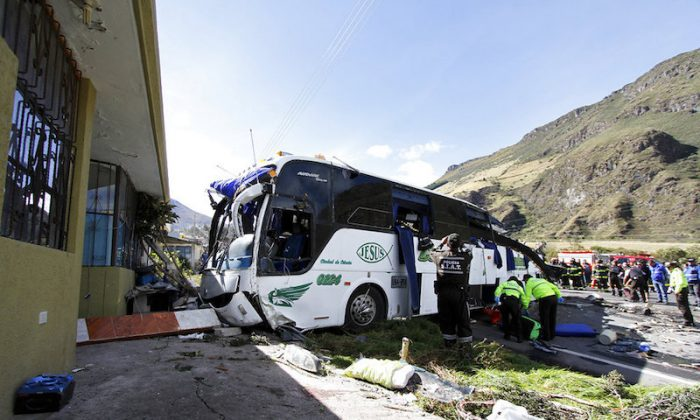 Police and rescue workers attend a Colombian-registered bus traveling to Quito that crashed in Pifo,, Ecuador,Tuesday, Aug. 14, 2018. At least 24 people were killed and another 19 injured when a bus careened into another vehicle at high speed and overturned along the Pifo-Papallacta highway, near Ecuador's capital, local officials reported. (AP/Carlos Noriega)