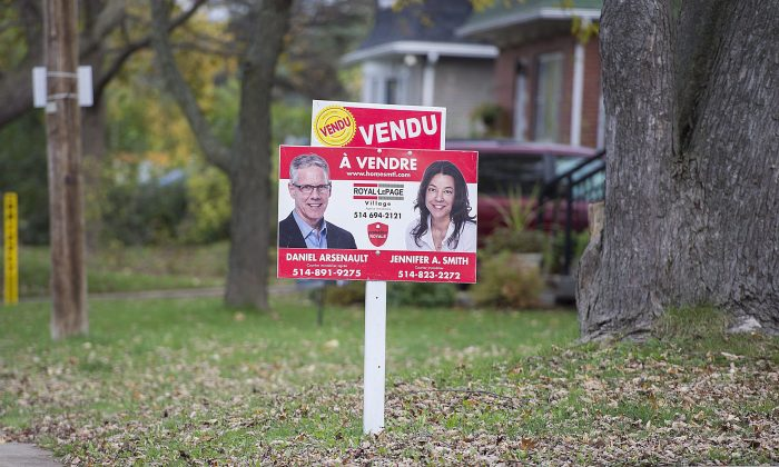 A sold sign is shown on the lawn of a residential property on the west island ofMontreal in this file photo. Canada's second largest city is in the midst of a strong upward trend of house price increases. (The Canadian Press/Graham Hughes)