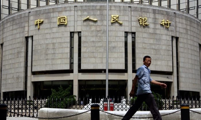 A pedestrian walks past the People's Bank of China, also known as China's Central Bank in Beijing, 22 August 2007. China's bid to tighten liquidity while most central banks worldwide are battling to boost cash flows underlines the Asian giant's status as largely immune from the troubles afflicting global markets. AFP PHOTO/TEH ENG KOON (Photo credit should read TEH ENG KOON/AFP/Getty Images)