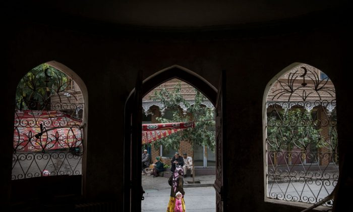 An ethnic Uyghur woman walks by a closed Islamic school on July 1, 2017 in the old town of Kashgar, in the far western Xinjiang province, China. (Kevin Frayer/Getty Images)