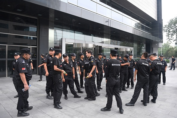 Security personnel stand in front an entrance of China's Banking Regulatory Commission to guard against protesters in Beijing on August 6, 2018. (GREG BAKER/AFP/Getty Images)