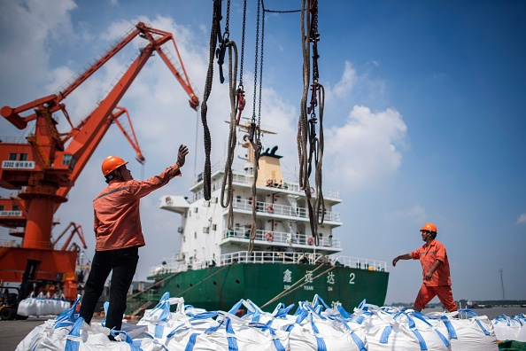 This photo taken on August 7, 2018 shows workers unloading bags of chemicals at a port in Zhangjiagang in China's eastern Jiangsu province. (JOHANNES EISELE/AFP/Getty Images)