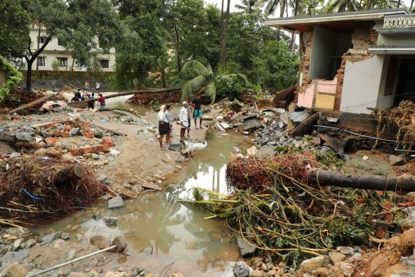 Indian residents look at houses destroyed by flood waters at Kannappankundu in Kozhikode, in the Indian state of Kerala on Aug. 10, 2018.