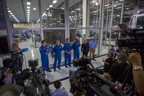 (L-R) NASA Astronauts Bob Behnken, Doug Hurley, Mike Hopkins and Victor Glover, and Director of Crew Mission Management Benji Reed talk to reporters in front of the Crew Dragon spacecraft, under construction in a clean room, during a media tour of SpaceX headquarters and rocket factory on Aug. 13, 2018 in Hawthorne, California. (David McNew/Getty Images)