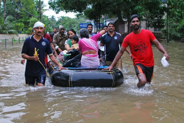 Indian volunteers and rescue personnel evacuate local residents in a boat in a residential area at Kozhikode, in the Indian state of Kerala, on Aug. 16, 2018.