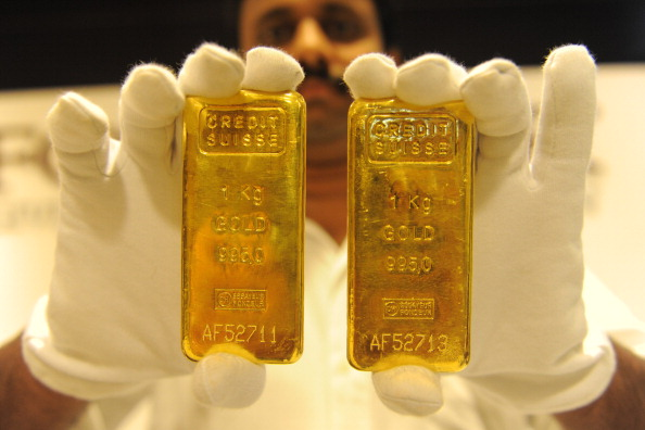 A jewellery shop employee displays 24-karat gold bars in Ahmedabad on Aug. 20, 2011. (SAM PANTHAKY/AFP/Getty Images)