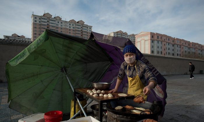 A street vendor cooks food as the sun rises over the city of Jiayuguan, Gansu Province, on April 22, 2016. (Nicolas Asfouri/AFP/Getty Images)