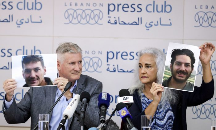 Marc (L) and Debra Tice, parents of U.S. journalist Austin Tice who was kidnapped in Syria in 2012, hold portraits of him during a press conference in the Lebanese capital Beirut on July 20, 2017. (JOSEPH EID/AFP/Getty Images)