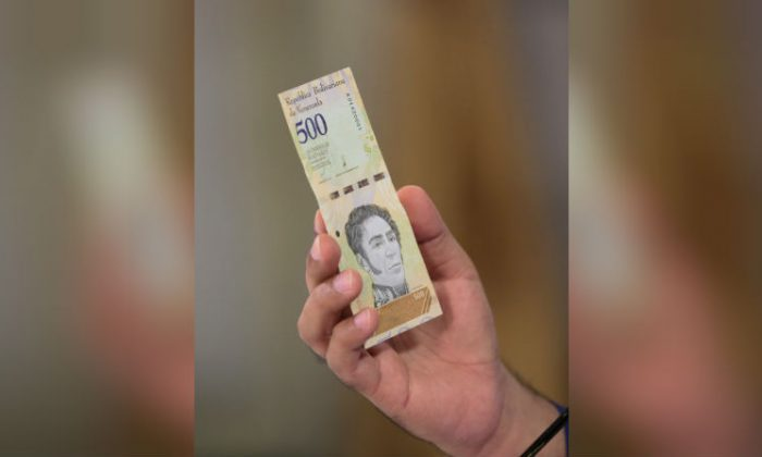 Venezuela's President Nicolas Maduro holds a bank note of the new Venezuela's currency Bolivar Soberano (Sovereign Bolivar) as he speaks during a meeting with ministers at Miraflores Palace in Caracas, Venezuela July 25, 2018. (Miraflores Palace/Reuters)