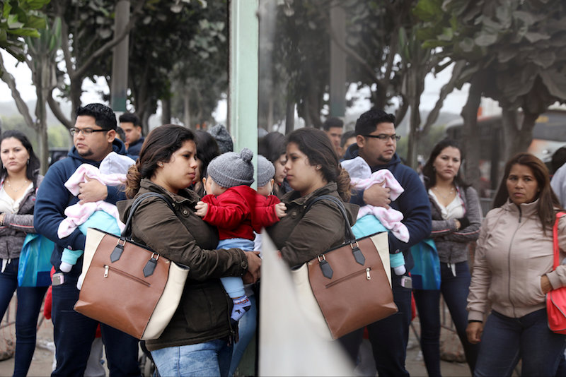 Venezuelan migrants wait at the Interpol headquarters to get paperwork needed for a temporary residency permit in Lima