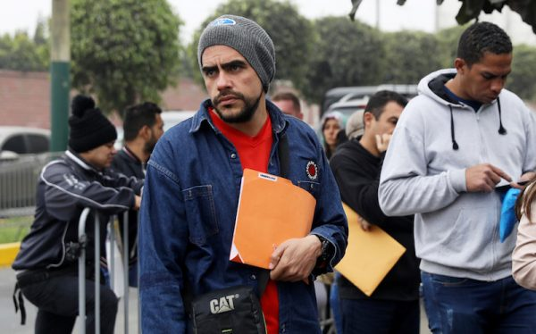 Venezuelan migrants wait at the Interpol headquarters in Lima to get paperwork needed for a temporary residency permit