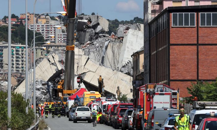 Firefighters and rescue workers stand at the site of collapsed Morandi Bridge in the port city of Genoa, Italy on Aug. 17, 2018. (Reuters/Stefano Rellandini)