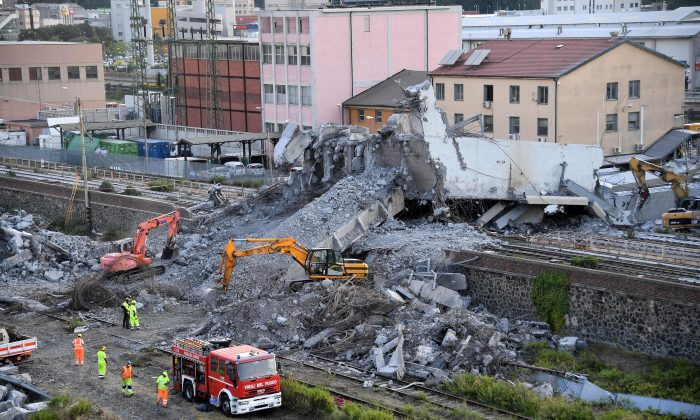 Firefighters remove debris of the collapsed Morandi highway bridge in Genoa, Italy, Aug. 16, 2018.