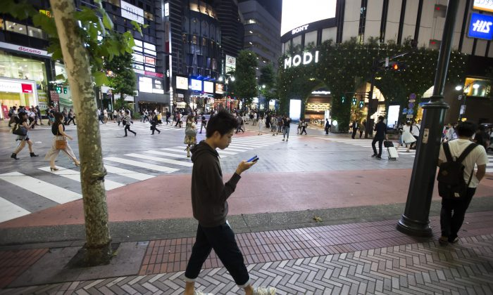 A man walks on a street as he plays games on his smartphone in Tokyo on July 22, 2016. Takahiro Hayashi's company Heroz develops intellectual games for smartphones using AI technology.    Tomohiro Ohsumi/Getty Images