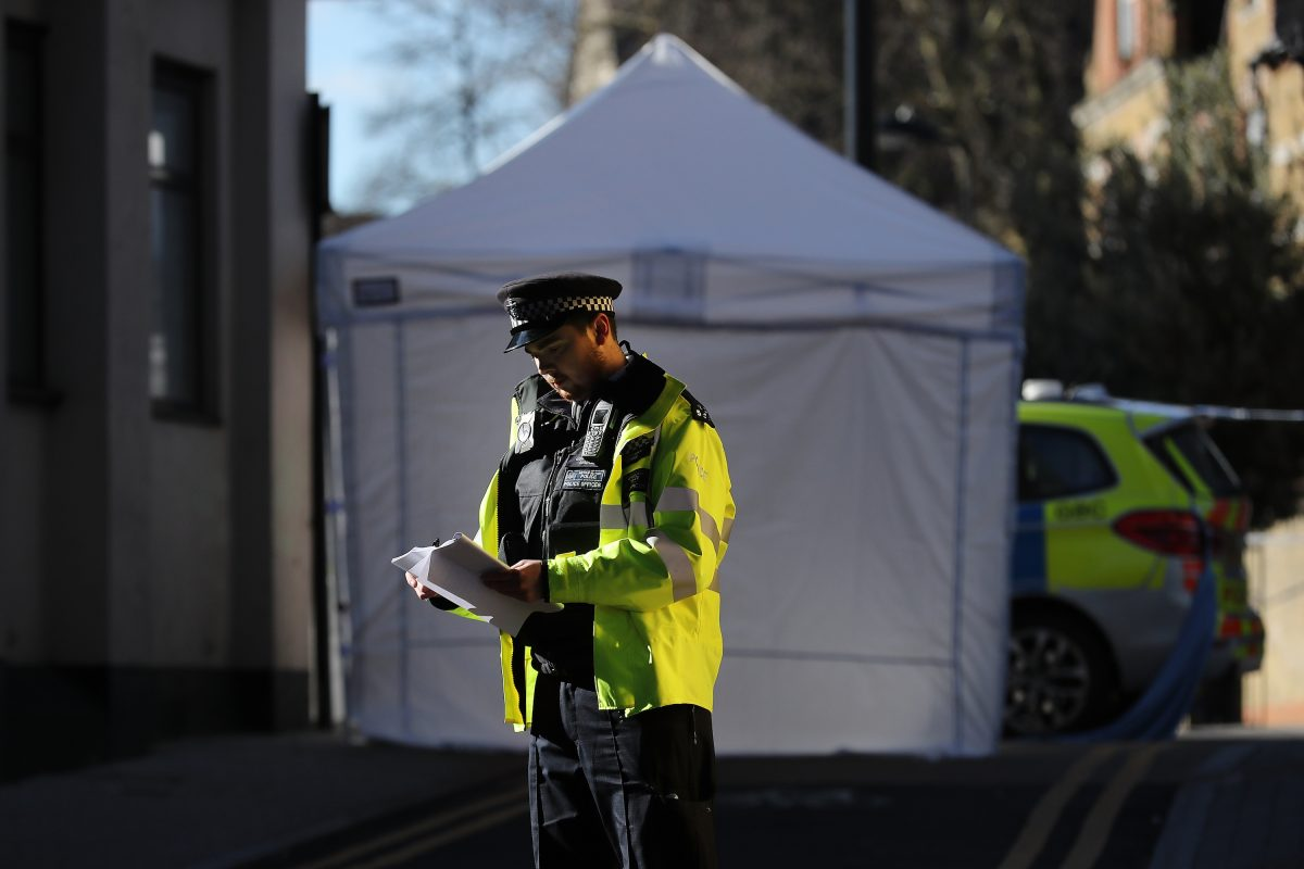 A British police officer stands at the scene of a knife crime in London