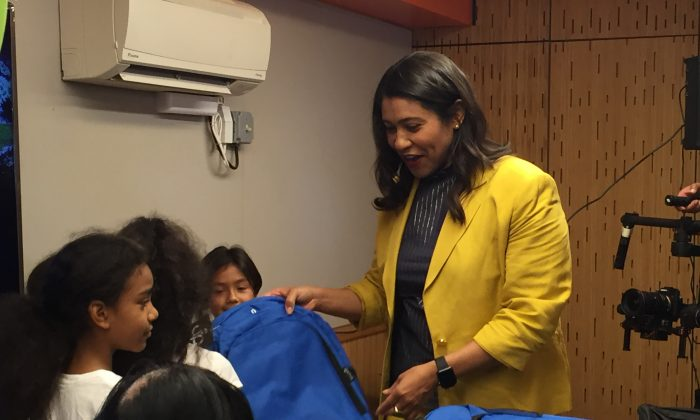 Mayor London Breed hands backpacks to children at Mayor's Annual Backpack Giveaway on August 16, 2018 (EETSF).