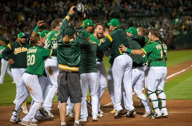 Oakland Athletics first baseman Matt Olson celebrates with team mates at home plate after hitting a walk off home run during the tenth inning of the game against. (Ed Szczepanski/USA Today Sports)