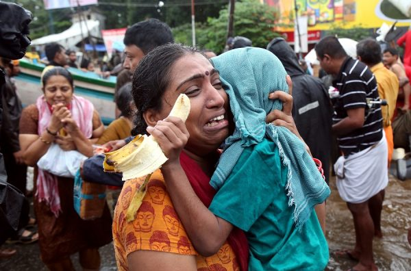 A woman cries as she holds her son after they were evacuated from a flooded area in Aluva in the southern state of Kerala, India on August 18, 2018. (Sivaram V/REUTERS)