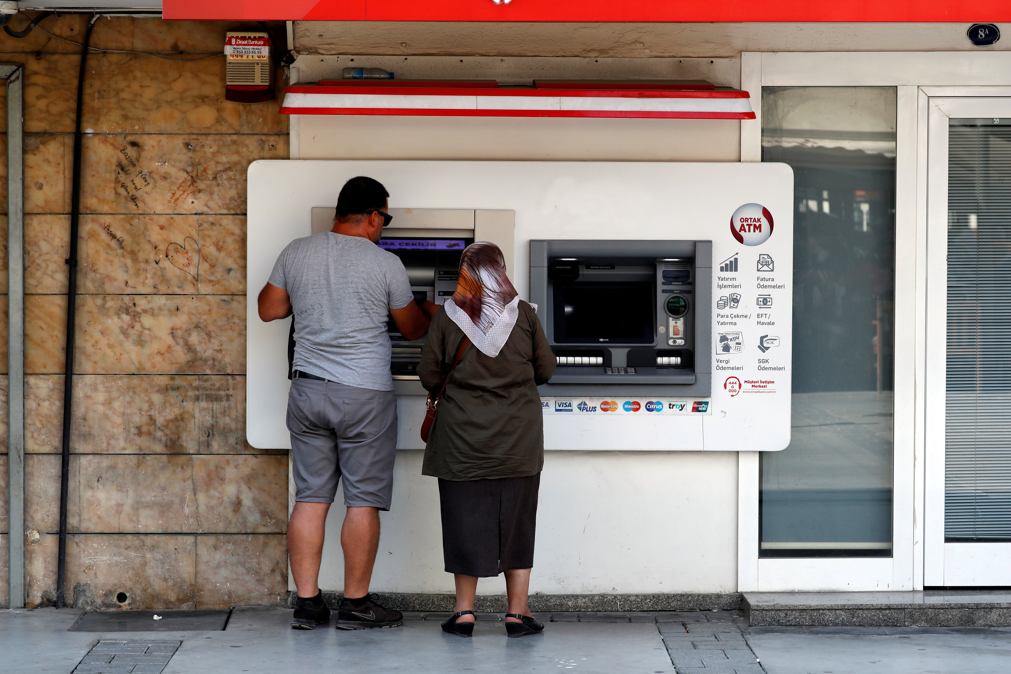 People withdraw money from a bank ATM in Izmir.