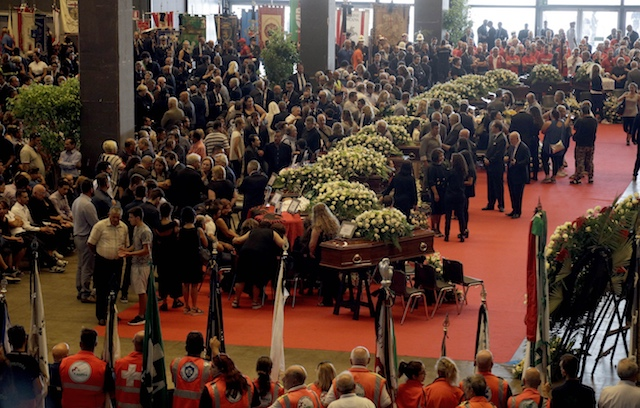 People gather for a funeral service for some of the victims of a collapsed highway bridge, in Genoa's exhibition center Fiera di Genova, Italy, on Aug. 18, 2018. (AP Photo/Gregorio Borgia)