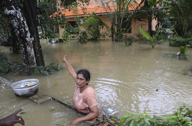 A stranded woman gestures towards her house as she asks for more essential supplies from a volunteer in a flooded area in Chengannur in the southern state of Kerala, India, on Aug.19, 2018. (AP Photo/Aijaz Rahi)