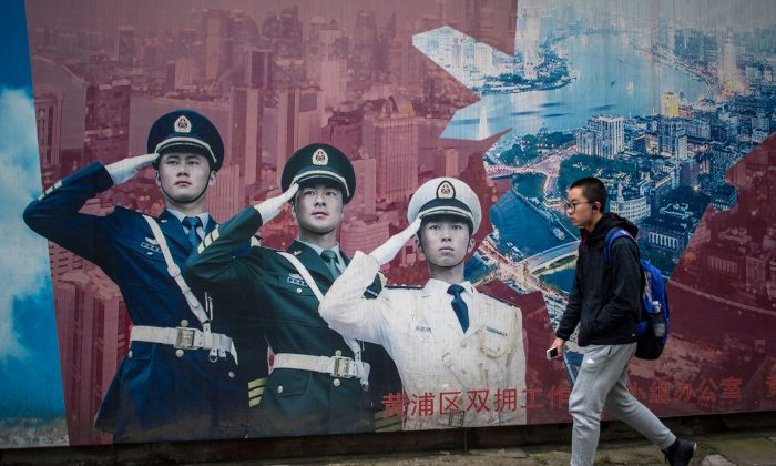 A man passes by a military propaganda poster in Shanghai on March 5, 2017. (JOHANNES EISELE/AFP/Getty Images)
