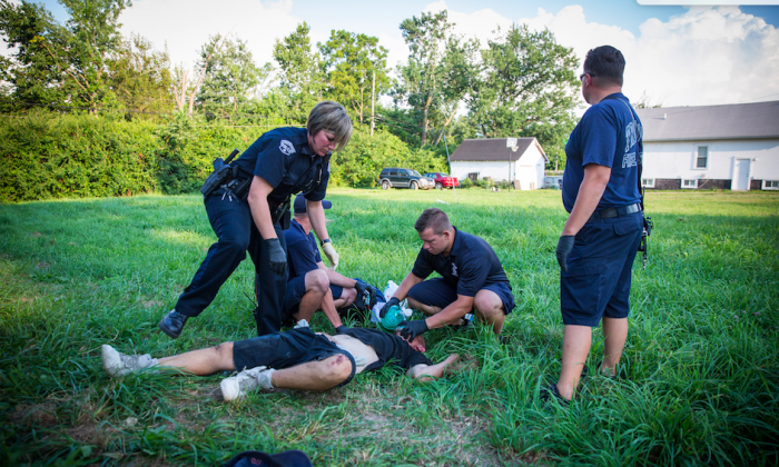 Local police and paramedics administer opioid-blocker Narcan to revive a man who is overdosing in the Drexel neighborhood of Dayton, Ohio, on Aug. 3, 2017. (Benjamin Chasteen/The Epoch Times)