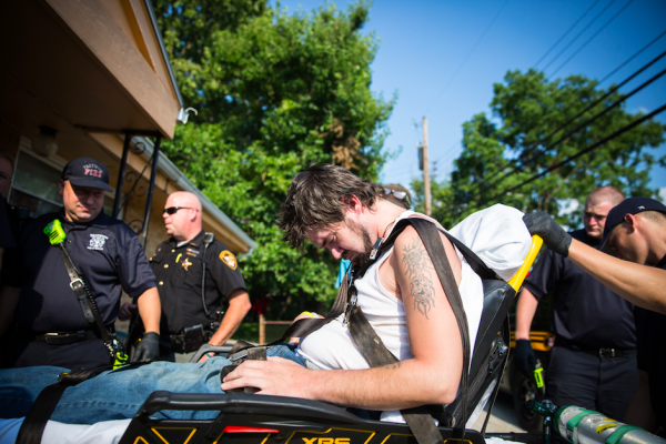 Local law enforcement and emergency services assist a man who is overdosing in the Drexel neighborhood of Dayton, Ohio, on Aug. 3, 2017. (Benjamin Chasteen/The Epoch Times)